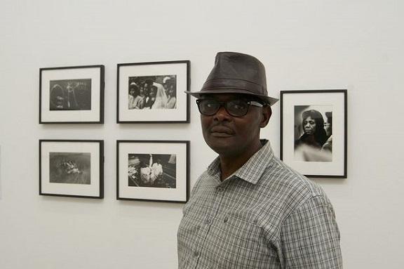 Portrait photograph of Vanley Burke in front of framed photographs