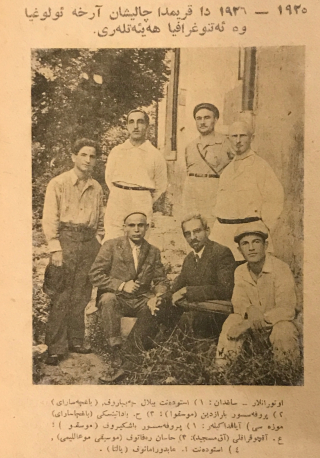 A group portrait photograph in black and white showing a line of men seated outside of a building in front of a line of four standing men, some of which are wearing hats, under a bolded title and above a caption, all of which are in Arabic script