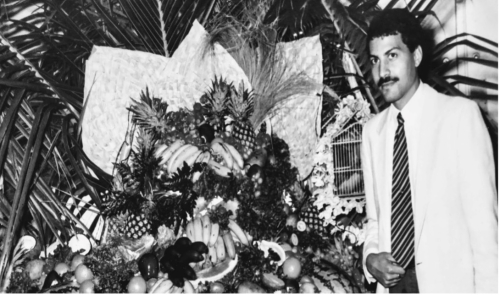 Black and white photograph of Rod standing infront of a tropical fruit display