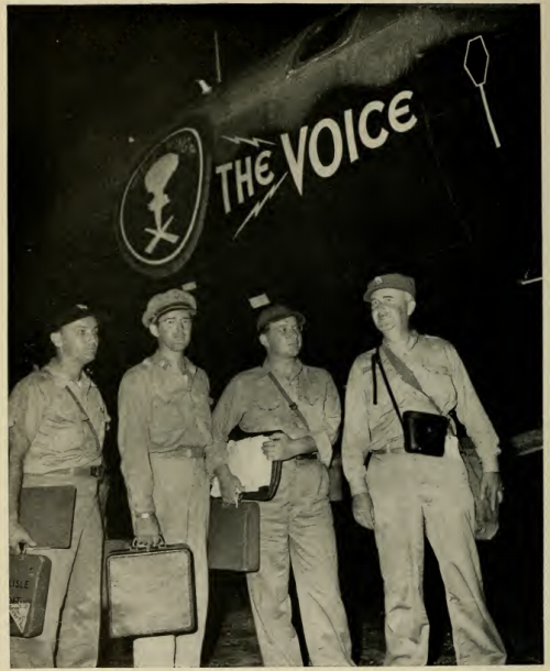 Four men stand with their bags in front of a plabe with The Voice written on the side of it.