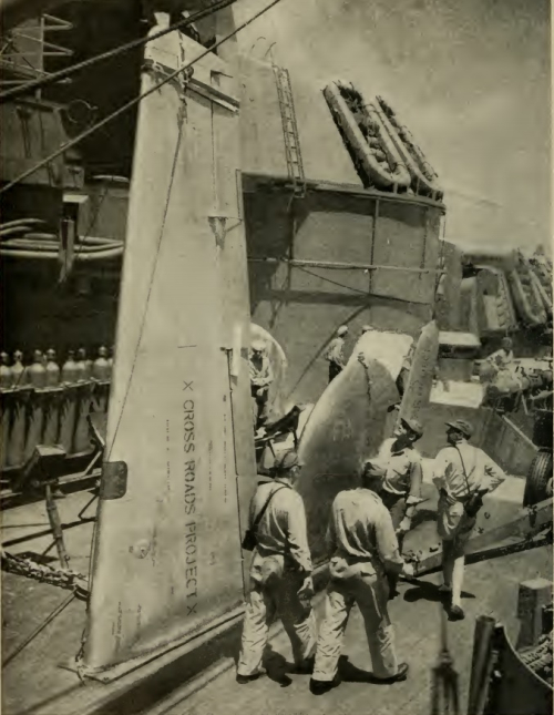 Men walk passed large equipment on board the ship's deck.