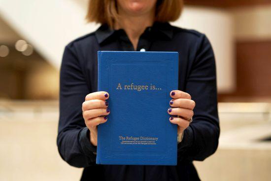 Emma Cherniavsky, UK for UNHCR CEO, holds The Refugee Dictionany