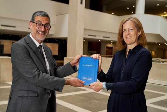 photograph of Emma Cherniavsky presenting The Refugee Dictionary to Xerxes Mazda at the British Library