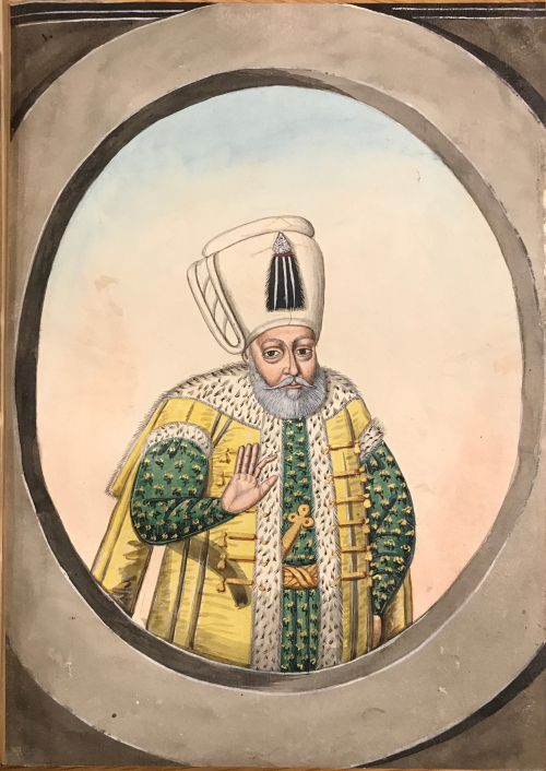An elderly man with a white beard in a green kaftan and gold belt under a yellow vest with an ermine trim. the man is wearing a white turban with a black tassel and is holding his right hand up