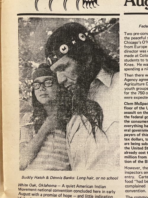 A black and white photograph of a man with long dark hair, with a boy with long hair and glasses standing to the left. Both wear headbands.
