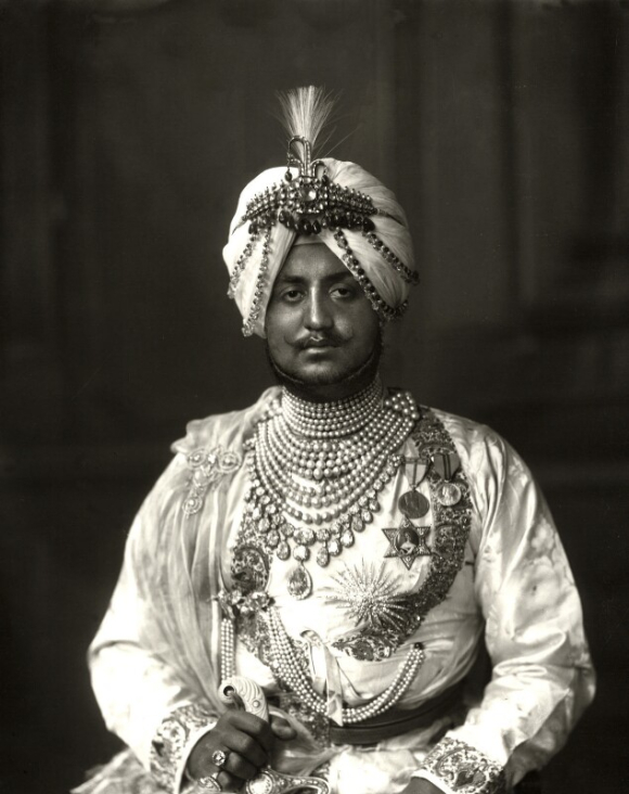 Photographic portrait of the Maharaja of Patiala wearing a turban and clothing bedecked with jewels and medals