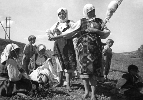 Black and white photo of two women standing and two seated, all in traditional Turkish dress and head coverings, in front of three children. The woman on the far right is holding a spindle and is pulling raw wool from it