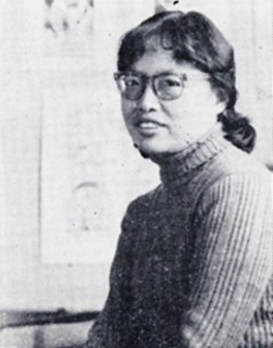 A black and white photograph of a women from the waist up. She is wearing a ribbed sweater, has her hair in a ponytail and is wearing glasses.