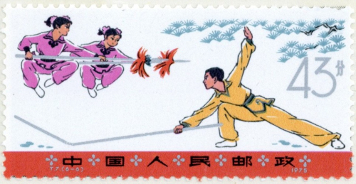 A colour postage stamp showing two young women in pink jumping above a stick brandished by a man in yellow, who is lunging at them.