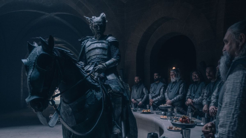 A still from the Green Knight movie, showing the Green Knight on horseback riding into King Arthur's courtsing into