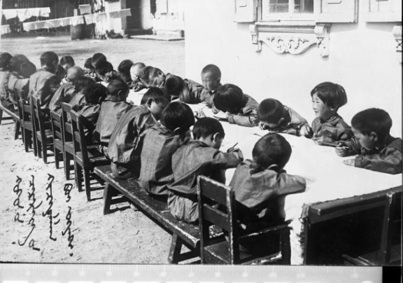 Photograph of children sitting around a large table. They are all concentrating and writing