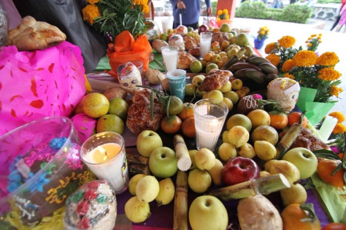 A photograph showing a detail of a Day of the Dead altar in Mexico, the image shows candles, apples, guavas, oranges, tangerines, bananas, marigold flowers, decorated sugar skulls and colourful perforated tissue paper.